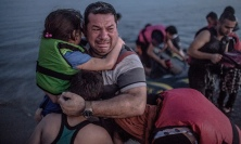 A Syrian refugee holding his son and daughter